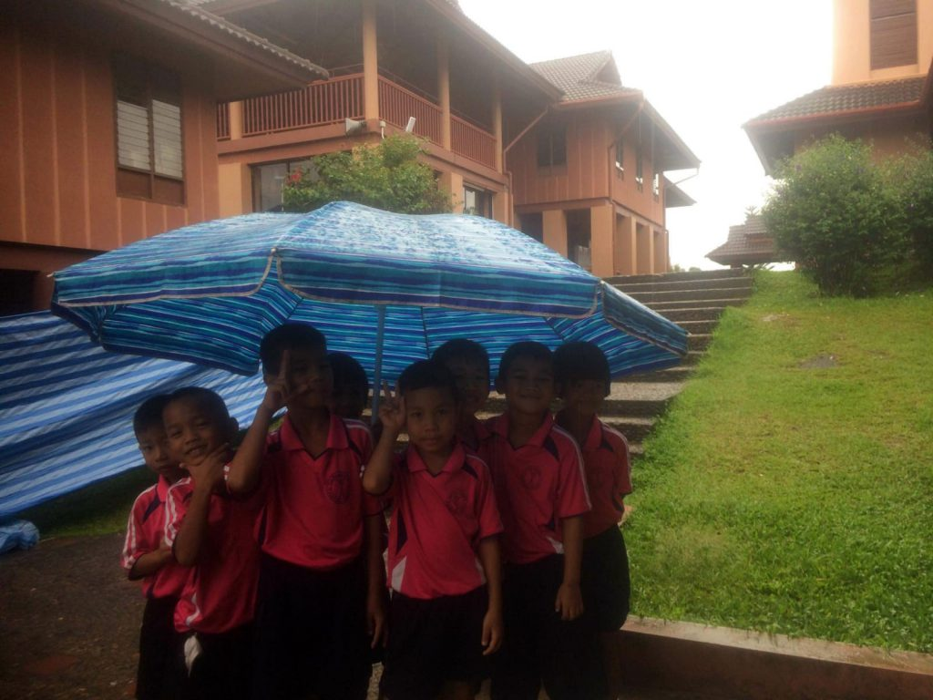 When raining, groups of children can use large umbrellas when walking to their classrooms.